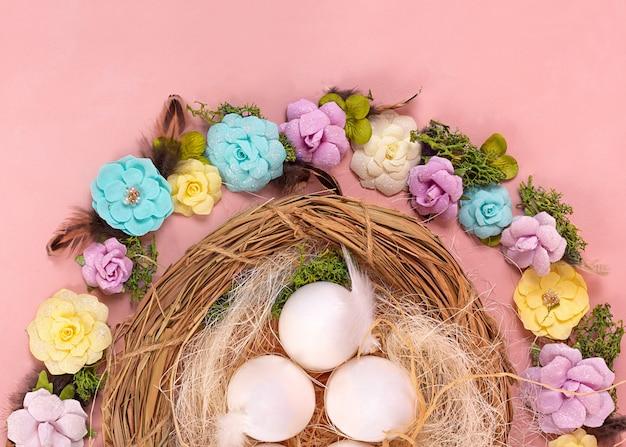 Humor de primavera, decoração de páscoa de ovos, flores de papel, uma coroa de videiras em um fundo de coral vivo. faixa larga - imagem.