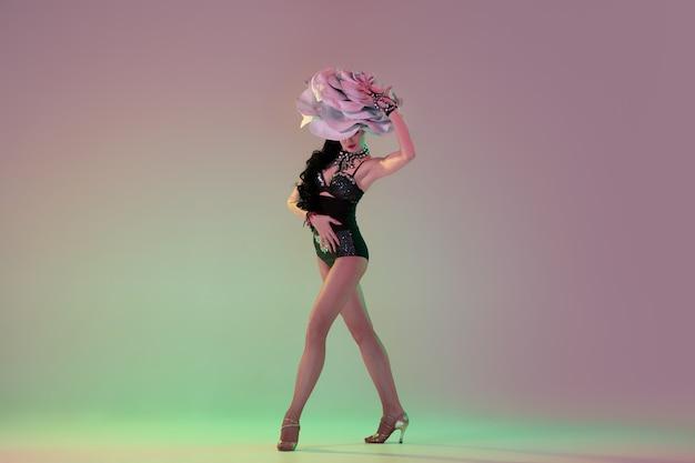 Humor de primavera. jovem dançarina com enormes chapéus florais em luz de néon na parede gradiente. modelo gracioso, mulher dançando, posando. conceito de carnaval, beleza, movimento, florescência, moda primavera.
