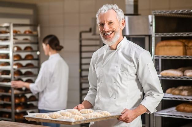 Humor de trabalho. homem adulto de cabelos grisalhos e feliz uniformizado com bandeja de pães e mulher atrás de uma prateleira de pão trabalhando em uma padaria