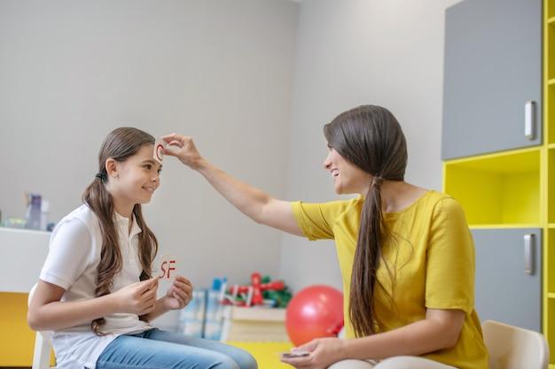 Humor divertido. psicóloga sorridente e alegre, conduzindo terapia lúdica com uma garota sociável e alegre, usando cartas