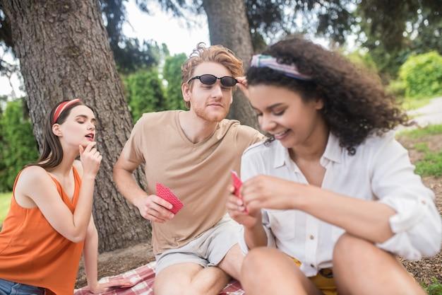 Humor divertido. três jovens amigos felizes se divertindo jogando cartas sentados no cobertor ao ar livre num dia de verão