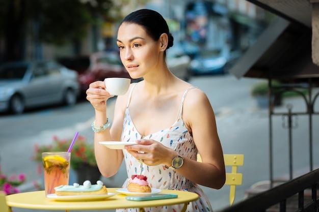 Humor do café. jovem pensativo sentado sozinho no terraço de um café e tomando café calmamente
