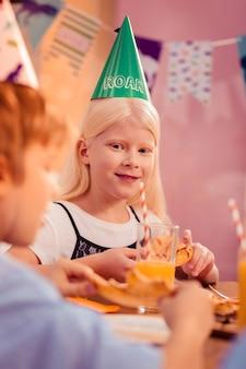 Humor festivo. positivo pequena mulher encantada sentada no meio da mesa enquanto olha para seu colega de classe