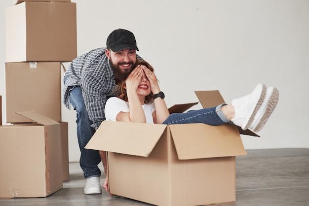 Humor lúdico. casal feliz juntos em sua nova casa. concepção de movimento
