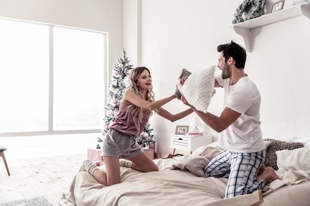 Humor lúdico. jovem barbudo bonito e sua esposa usando meias brancas grossas se divertindo com travesseiros