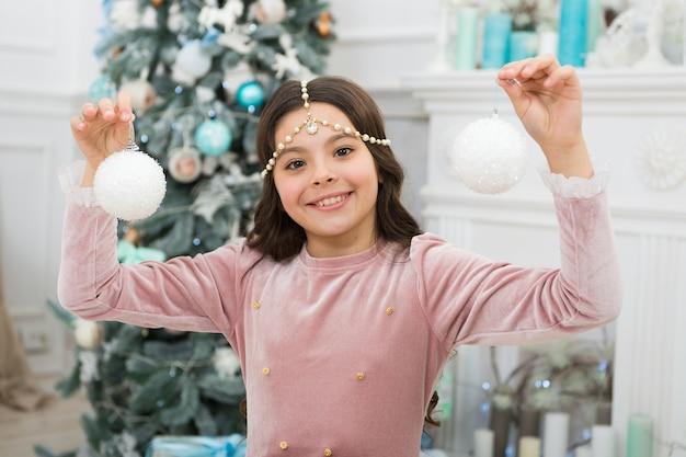 Humor lúdico. véspera de ano novo. sonhos se tornam realidade. idéias de decoração de natal. menina sorridente criança segurar enfeite de natal. adorável garota alegre fazendo desejo perto do interior decorado da árvore de natal.