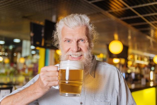 Humor maravilhoso. homem alegre e positivo sorrindo para você enquanto segura um copo de cerveja