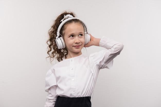 Humor maravilhoso. linda garota tocando seus fones de ouvido enquanto ouve a música