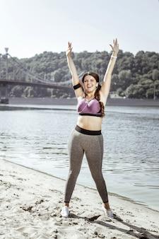 Humor maravilhoso. mulher alegre e positiva levantando as mãos em pé na praia
