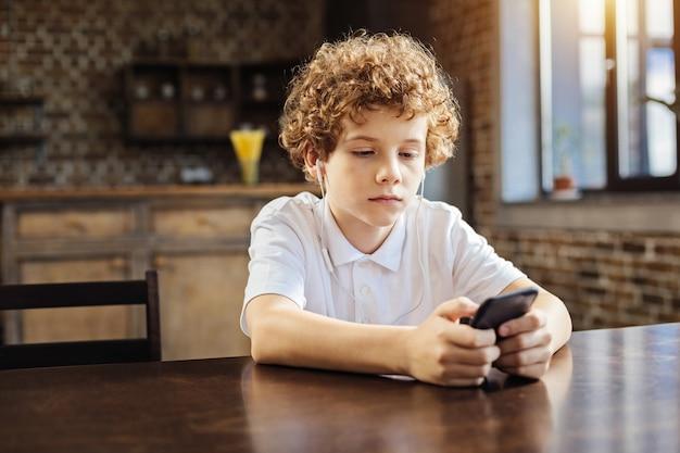 Humor nostálgico. rapaz sério pré-adolescente sentado a uma mesa e focando sua atenção em uma tela em um smartphone enquanto ouve a música tocando em seus fones de ouvido.