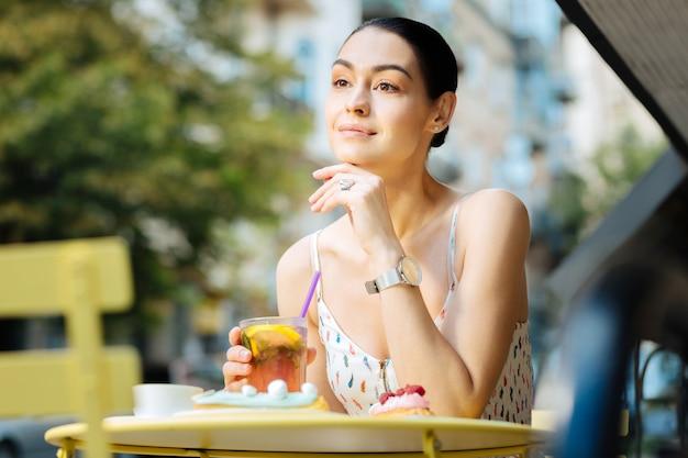 Humor pacífico. mulher jovem relaxada, bonita e sorridente, sentada à mesinha com um copo de limonada fresca na mão