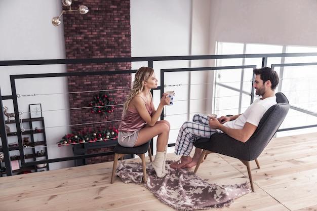 Humor pacífico. mulher loira magra de cabelos compridos em uma bela lingerie parecendo calma enquanto toma chocolate com marshmallow