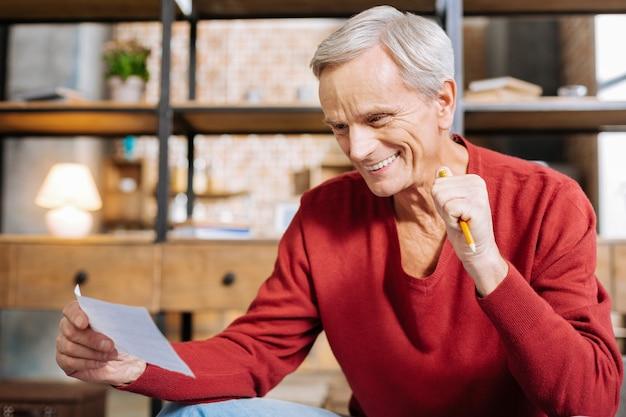 Humor positivo. homem alegre feliz encantado segurando um lápis e sorrindo enquanto está de bom humor