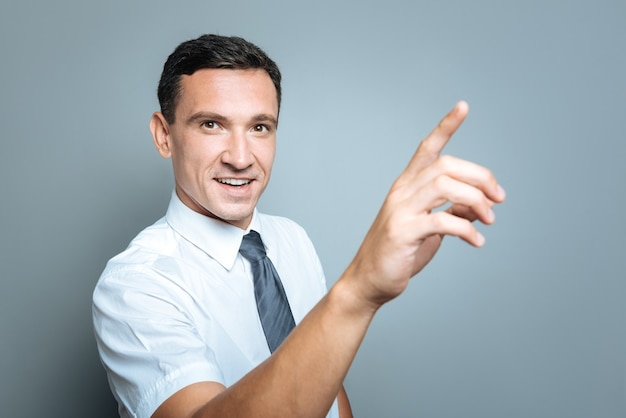 Humor positivo. homem bonito e encantador segurando a mão para cima e sorrindo enquanto olha para você