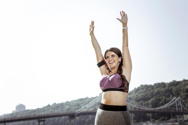 Humor positivo. mulher alegre e encantada, levantando as mãos enquanto se sente muito feliz