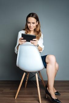 Humor positivo. mulher atraente e encantada segurando um tablet e usando-o enquanto descansa na cadeira