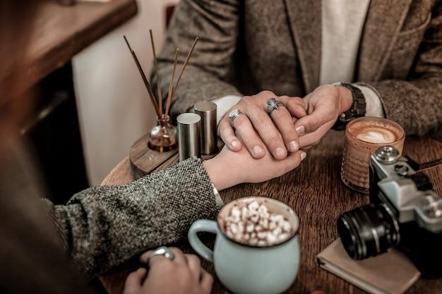 Humor romântico. homem de mãos dadas com uma mulher enquanto está sentado em um café