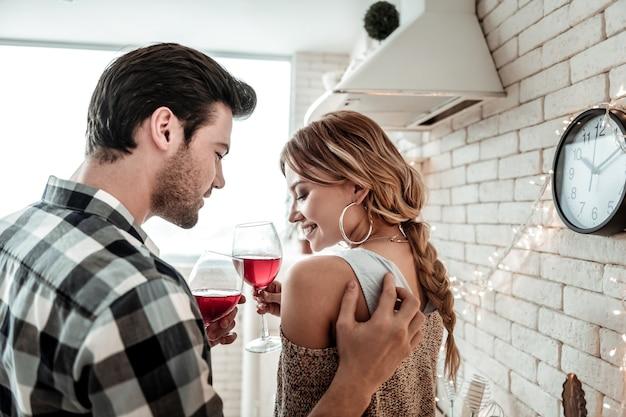 Humor romântico. jovem atraente de cabelos escuros, vestindo uma camisa xadrez e dizendo palavras agradáveis para a esposa