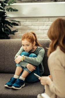 Humor sombrio. menina triste e desanimada colocando o queixo sobre os joelhos enquanto pensa em seus problemas