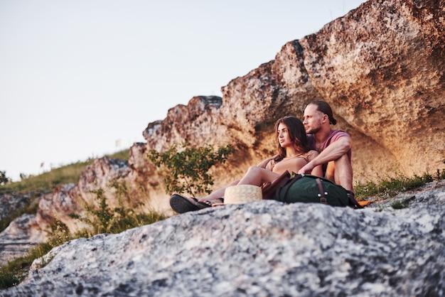 Humor sonhador. duas pessoas sentadas na rocha e observando a natureza deslumbrante.