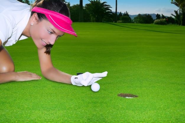 Humor verde da mulher do furo do golfe que passa rapidamente uma bola