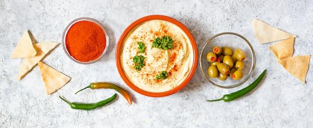 Humus caseiro saudável servido com páprica em pó, pão pita, azeitonas e salsa. cozinha do oriente médio, cozinha israelense, cozinha levanesa, cozinha levantina.