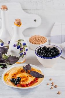 Húmus cremoso caseiro saudável com azeite, azeitonas pretas e manjericão na superfície de madeira branca. conceito de comida saudável e dieta.