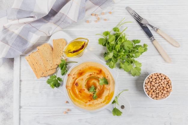 Húmus cremoso caseiro saudável com azeite, coentro, páprica defumada e pão crocante na superfície de madeira branca. conceito de comida saudável e dieta.