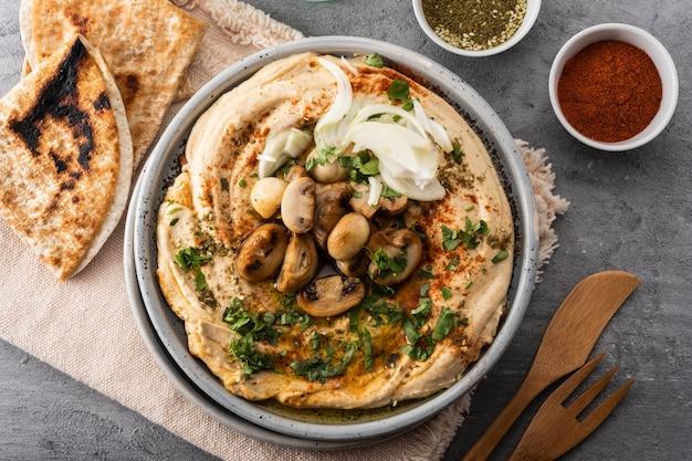 Humus mediterrâneo tradicional com cogumelos e cebolas. hummus clássico com páprica, azeite, cebola, cogumelos e temperos