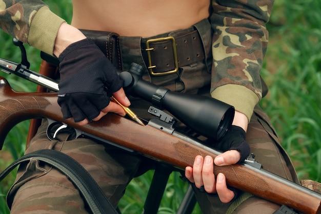 Hunter carregando bala na carabina com mira óptica