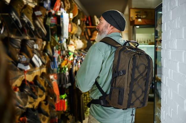 Hunter com mochila na vitrine da loja de armas