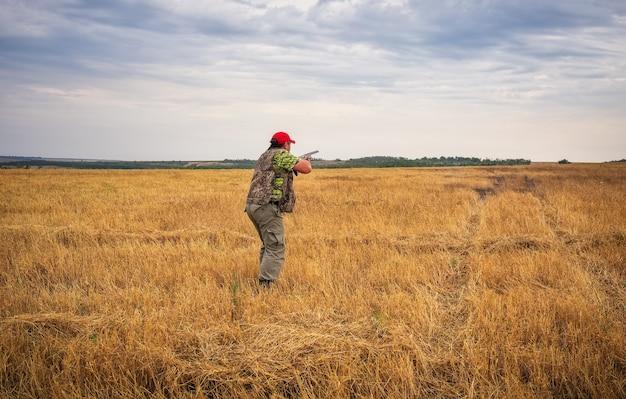 Hunter com uma arma no campo mirando na presa