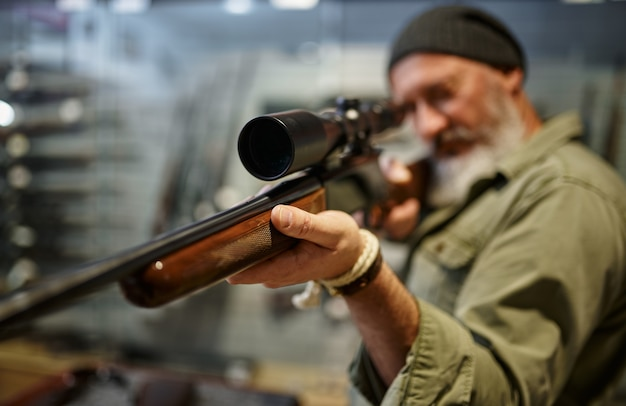 Hunter comprando rifle com mira óptica, loja de armas