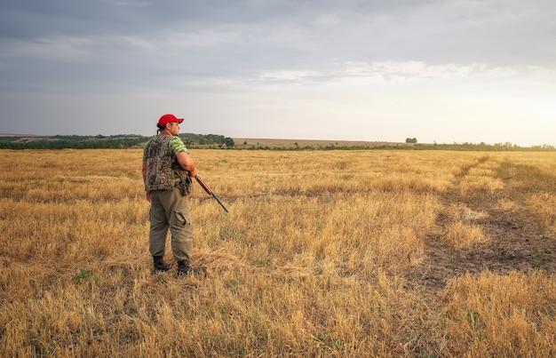 Hunter movendo-se com a espingarda à procura de uma presa. caça à lebre