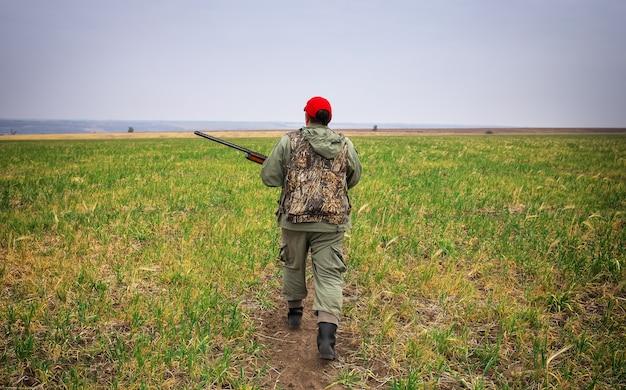 Hunter movendo-se com a espingarda à procura de uma presa. hunter com uma arma. caça à lebre