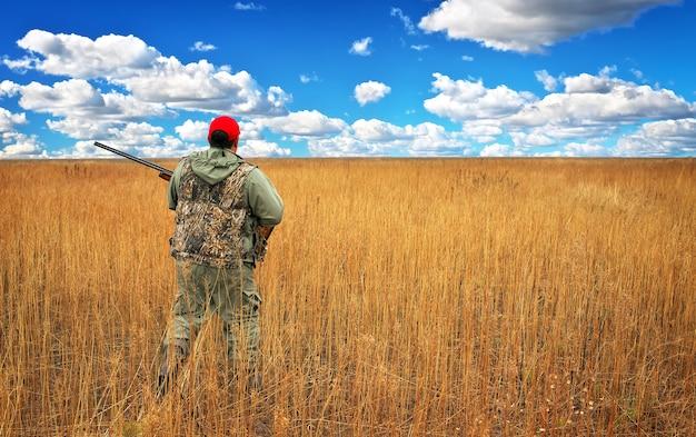 Hunter movendo-se com a espingarda à procura de uma presa no campo. hunter com uma arma. caça à lebre