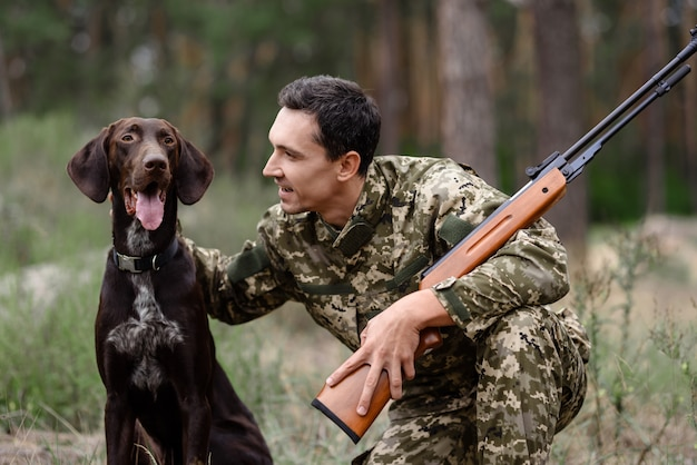 Hunter pets good dog homem com rifle na floresta.
