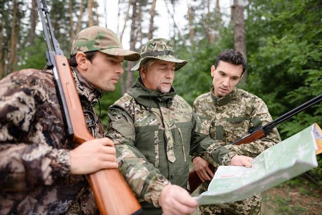 Hunters study hiking map determine a maneira na floresta.