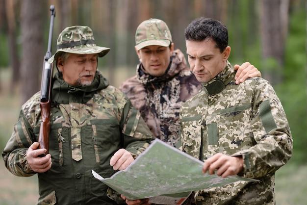 Hunters studying map orienteering bushcraft.