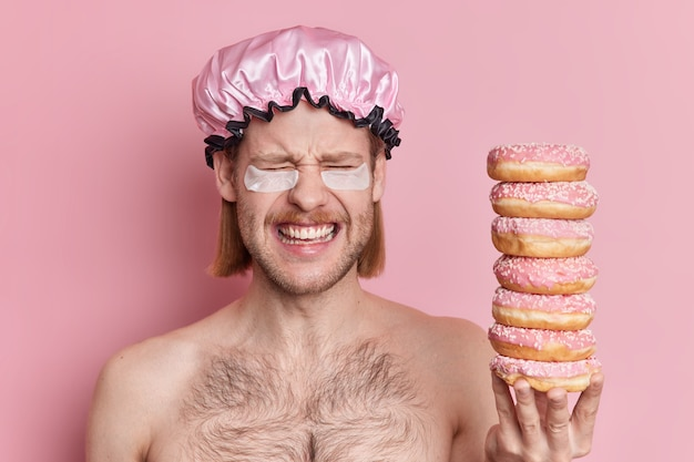 Huy alegre com bigode de cabelo comprido aplica adesivos de hidrogel sob os olhos segura uma pilha de donuts doces e deliciosos.