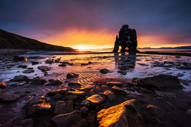 Hvitserkur 15 m de altura. é uma rocha espetacular no mar na costa norte da islândia. esta foto reflete na água após o pôr do sol da meia-noite.