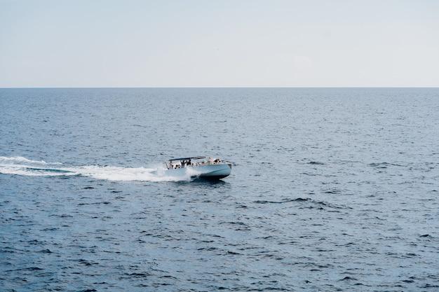 Iate a motor com turistas a bordo que navega em alto mar