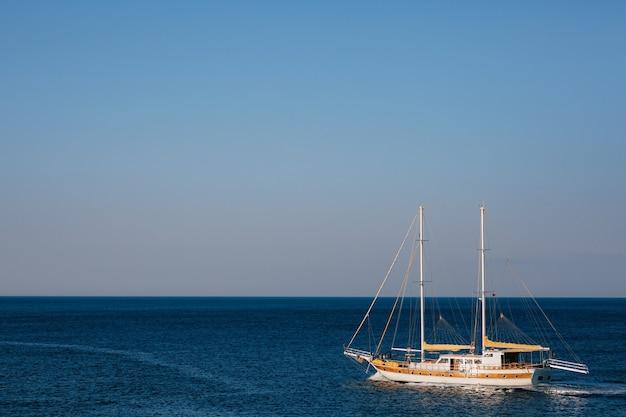 Iate à vela branco de dois mastros no fundo do mar azul
