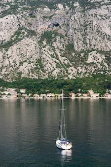 Iate à vela branco navega ao longo da baía de kotor, tendo como pano de fundo a vista das montanhas