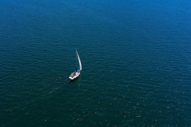 Iate à vela branco solitário no mar, vista aérea, tiro com drones