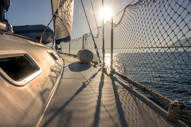 Iate à vela no mar em clima calmo. a vela de estai está de pé. luz de fundo do sol forte