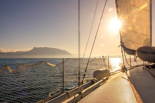 Iate à vela no mar em tempo ensolarado. a vela de estai está de pé. luz de fundo do sol forte
