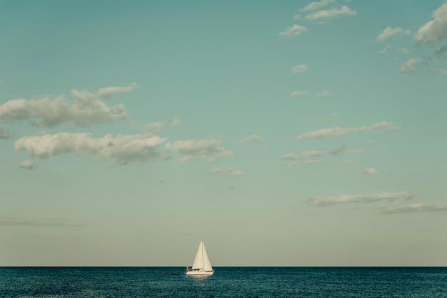 Iate branco no horizonte em um mar calmo