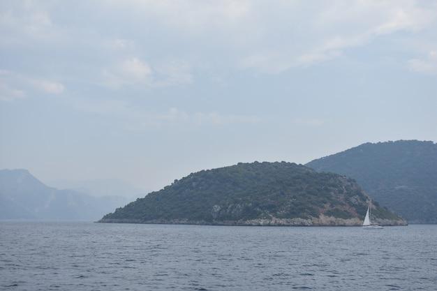 Iate com uma vela branca navega no mar, tendo como pano de fundo as montanhas