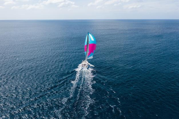 Iate com uma vela colorida no mar